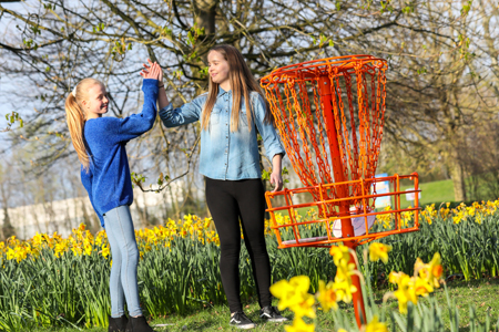 Illustration of two girls playing disc golf in the Town Park